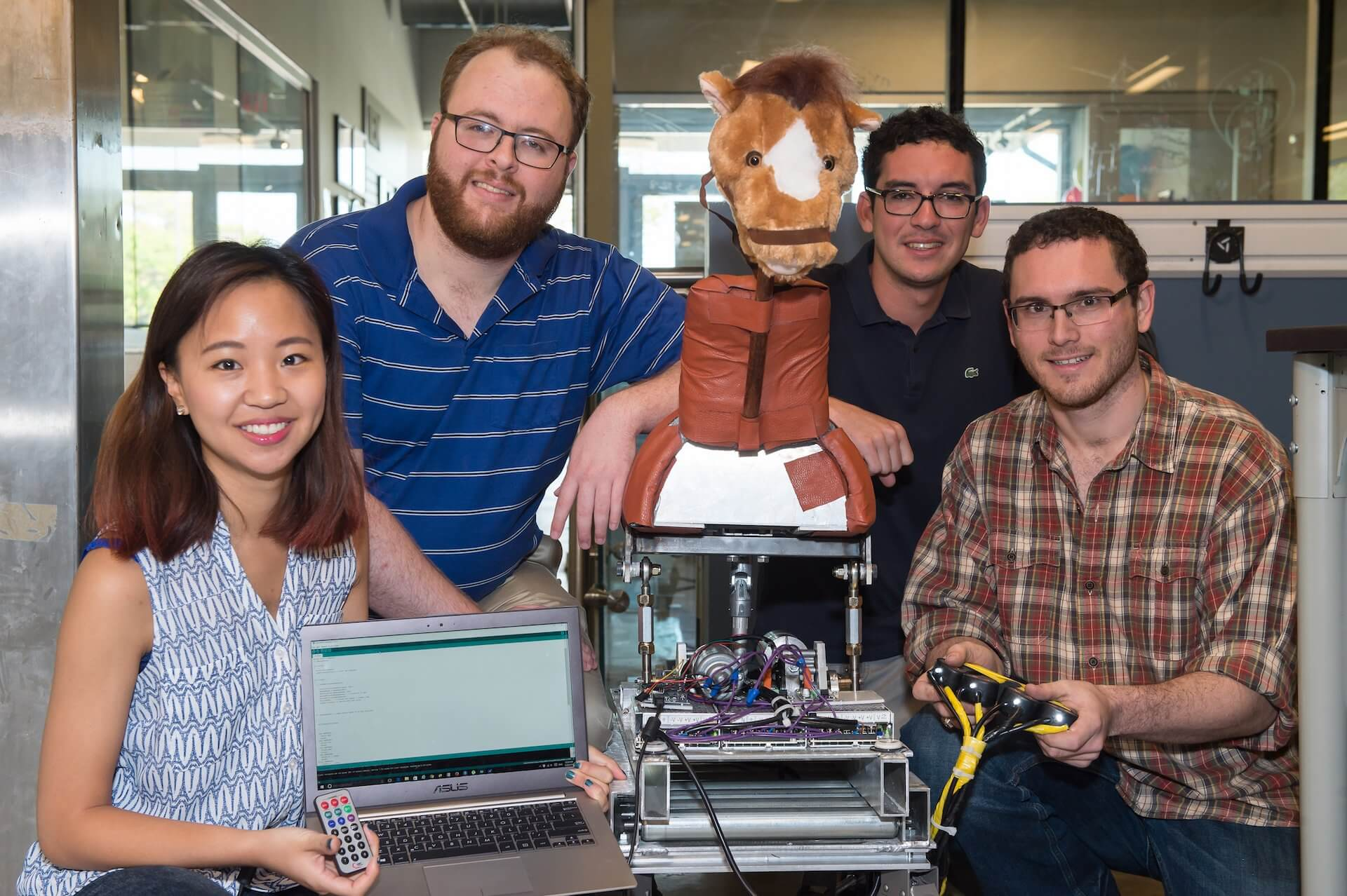 The Hippo Riders team of Rice University engineering students has created a horse simulator for use by hippotherapy patients. From left: Amy Ryu, Erik Hansen, Jaime Gomez and Brett Berger. (Credit: Jeff Fitlow/Rice University)