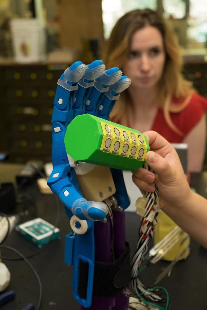 Rice University engineering student Rachel Sterling monitors as a teammate lines up an object to test the force applied by a 3-D printed hand. Rice students have assembled a suite of tools to validate how well printed hands transfer force from the wearer to the object being gripped.