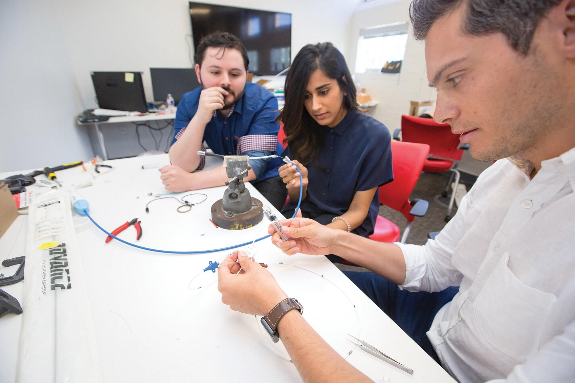 From left, Alex Arevalos, Ph.D., Avni Patel, M.E., and Jacob Kriegel, M.D., co-founders of Alleviant Medical, demonstrate their device, which cuts a hole in the wall separating the left and right atria to alleviate a build-up of pressure in the heart.