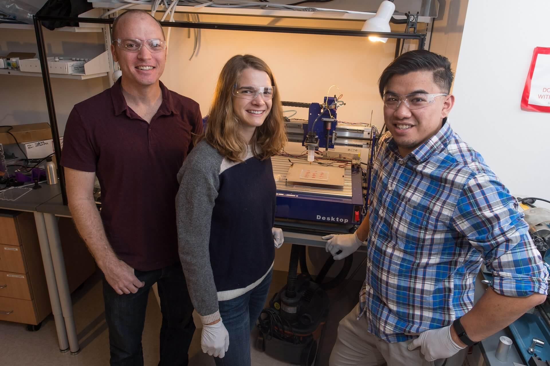 From left, Jordan Miller, Samantha Paulsen and Anderson Ta stand with the 3-D printer they used to create the silicone constructs. (Photo by Jeff Fitlow)
