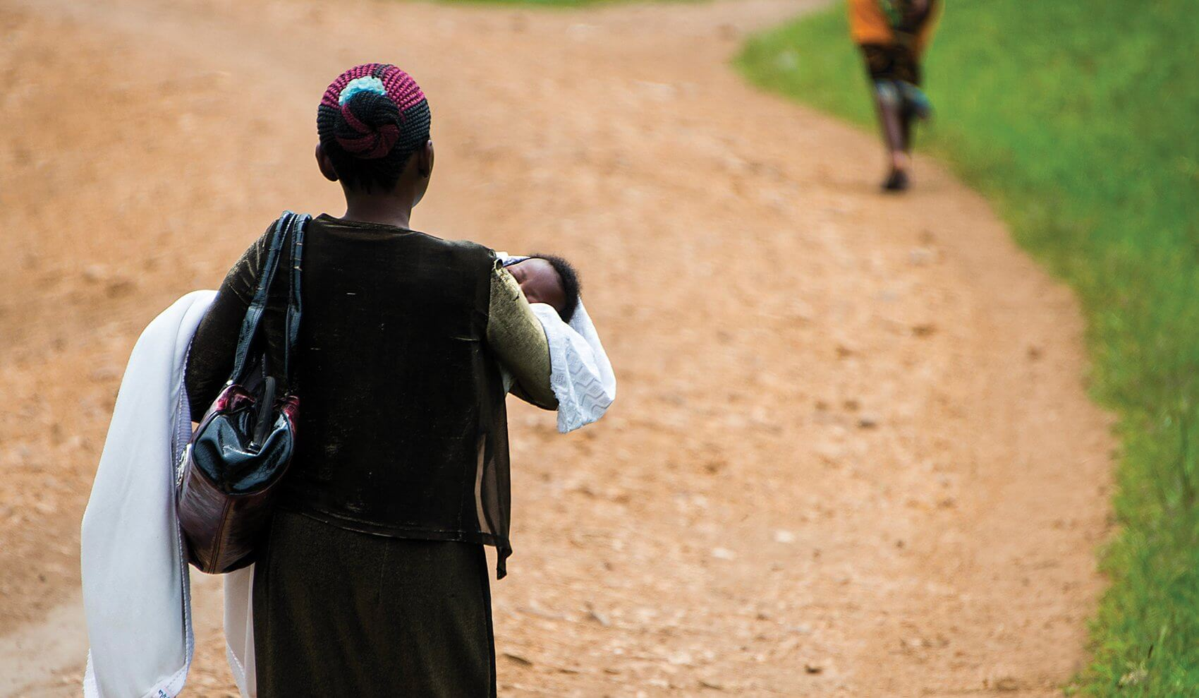 A mother carries her child to a checkup in Uganda. (Credit: Smiley Pool)