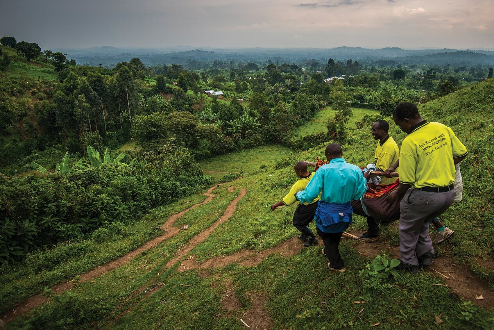 After going into labor, a young mother is carried down from her mountaintop village in Uganda to a hospital—a trip that lasts just 30 minutes. The Baylor International Pediatric AIDS Initiative has been working in Uganda to reduce the maternal and infant mortality rate. (Credit: Smiley Pool)