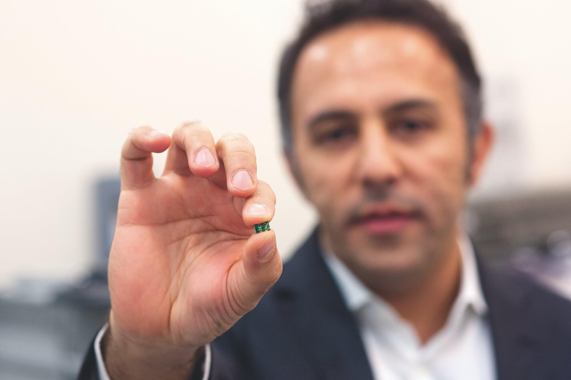 Aydin Babakhani, Ph.D., formerly of Rice University and now associate professor of electrical and computer engineering at the University of California at Los Angeles, holds the pacemaker chip.