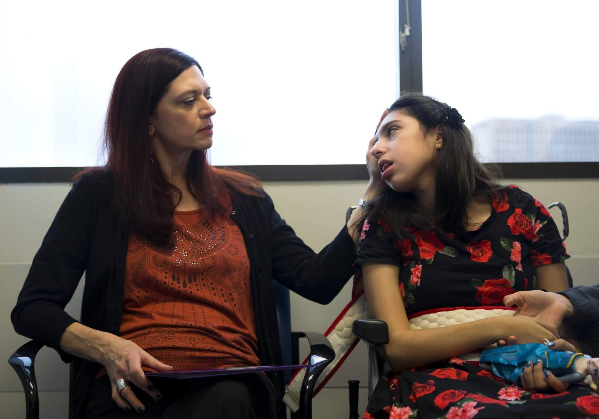 Sarah Ybarra strokes her daughter Kristin's hair during an appointment with Dr. Rebecca Schultz at Texas Children's Hospital. (Photo: Annie Mulligan.)
