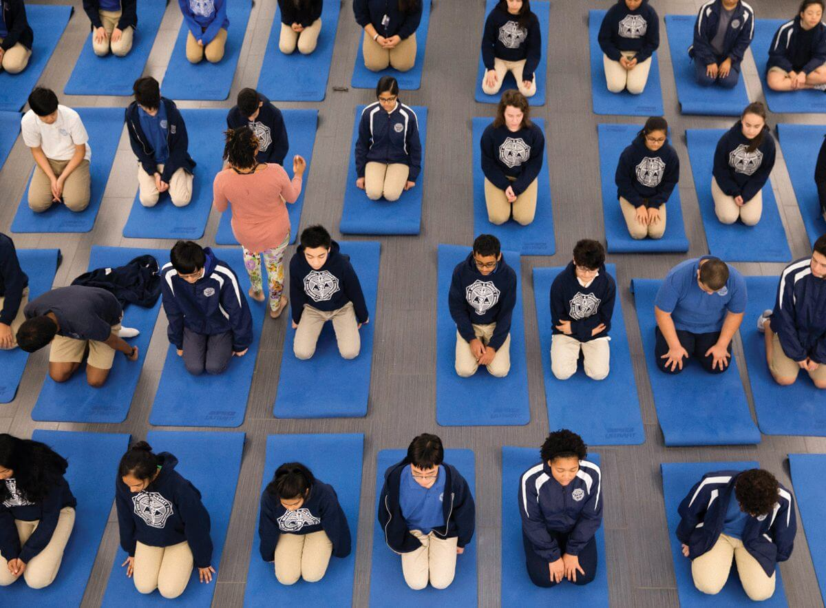 Ninth-graders at DeBakey High School practice yoga in the cafeteria (Credit: Annie Mulligan).
