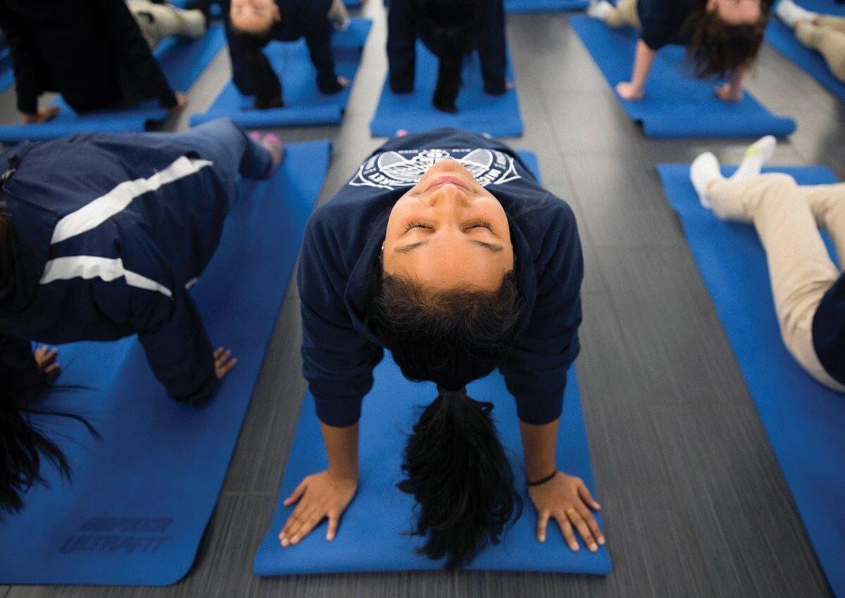 Freshman Sunaina Ayyagari holds a yoga pose during health science class at DeBakey High School (Credit: Annie Mulligan).