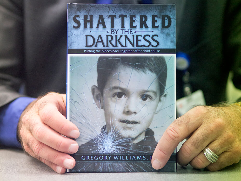 Gregory Williams, Ph.D., holds a copy of his book, Shattered by the Darkness.