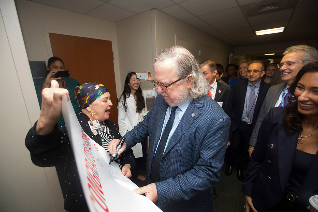 James P. Allison, Ph.D., an immunologist at The University of Texas MD Anderson Cancer Center who was jointly awarded the 2018 Nobel Prize in Physiology or Medicine this week, stops to sign a poster during a parade in his honor through MD Anderson's Main Building on Oct. 5, 2018. (Credit: Cody Duty, TMC News)