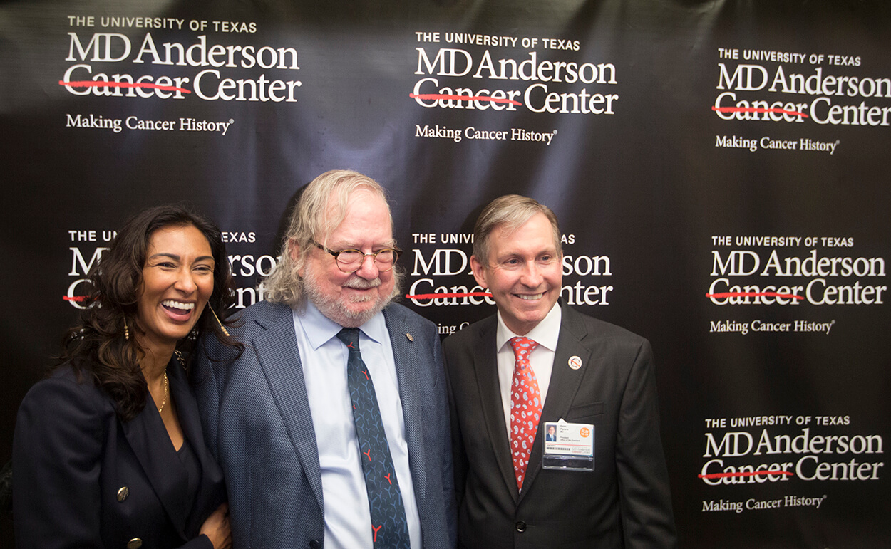 James P. Allison, Ph.D., (center), an immunologist at The University of Texas MD Anderson Cancer Center who was jointly awarded the 2018 Nobel Prize in Physiology or Medicine this week, smiles during a news conference after a parade in his honor through MD Anderson's Main Building on Oct. 5, 2018. Allison is with his wife, MD Anderson cancer researcher Pam Sharma, M.D., Ph.D., and MD Anderson President Peter Pisters, M.D. (Credit: Cody Duty, TMC News)