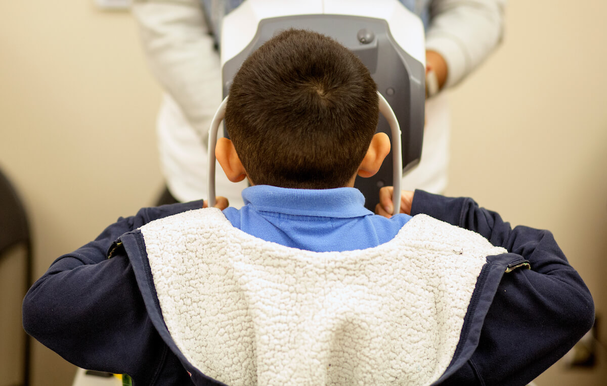 A student receives a vision evaluation during