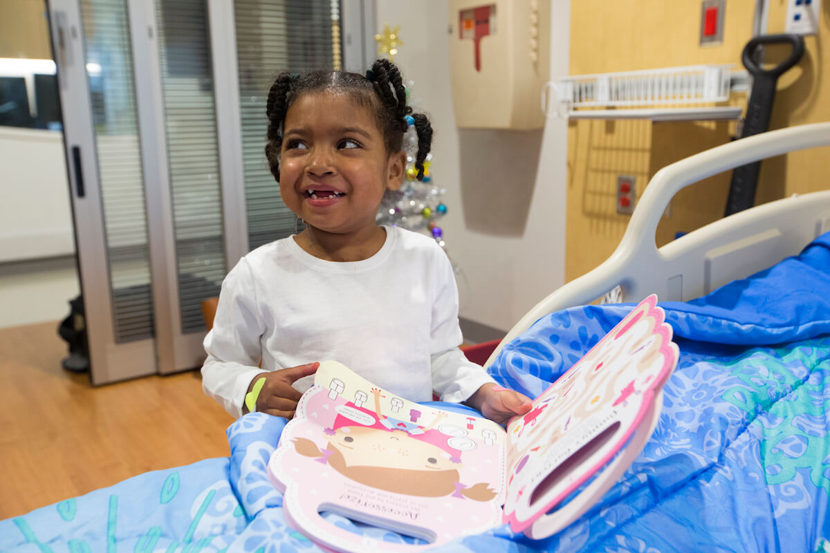 Hickman looks through a new book as she recovers from her heart transplant at Texas Children's Hospital.