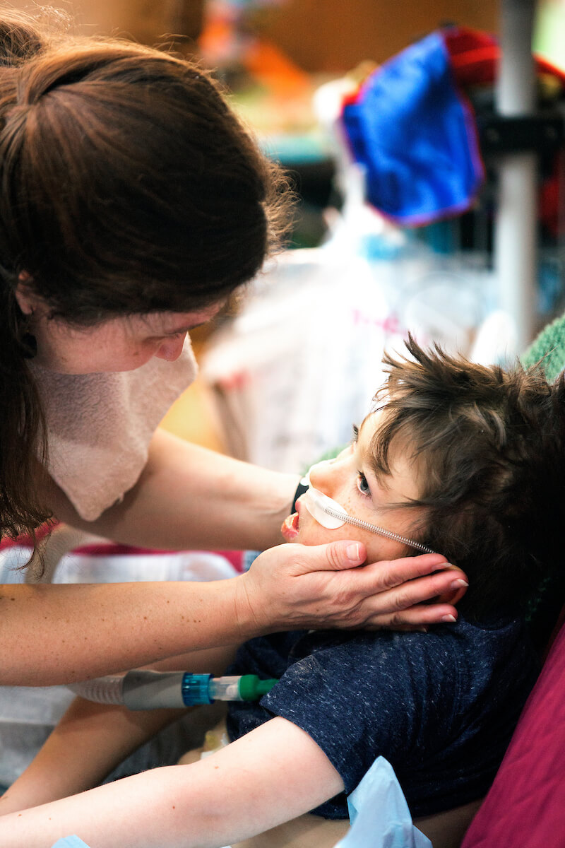 Cheryl Lingenfelter caresses the face of her son, 6-year-old Nathan Lingenfelter, who is part of the UT Physicians High Risk Children's Clinic's telemedicine study.