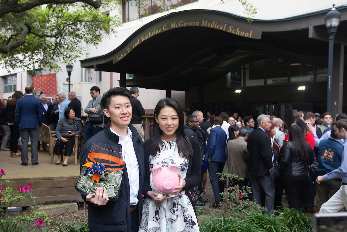 Charlie Wan, left, with girlfriend, Angela Liang, during Match Day at UTHealth's McGovern Medical School on March 15, 2019. Each student puts one dollar in the jar and the last person who is called to receive an envelope also snags the money.