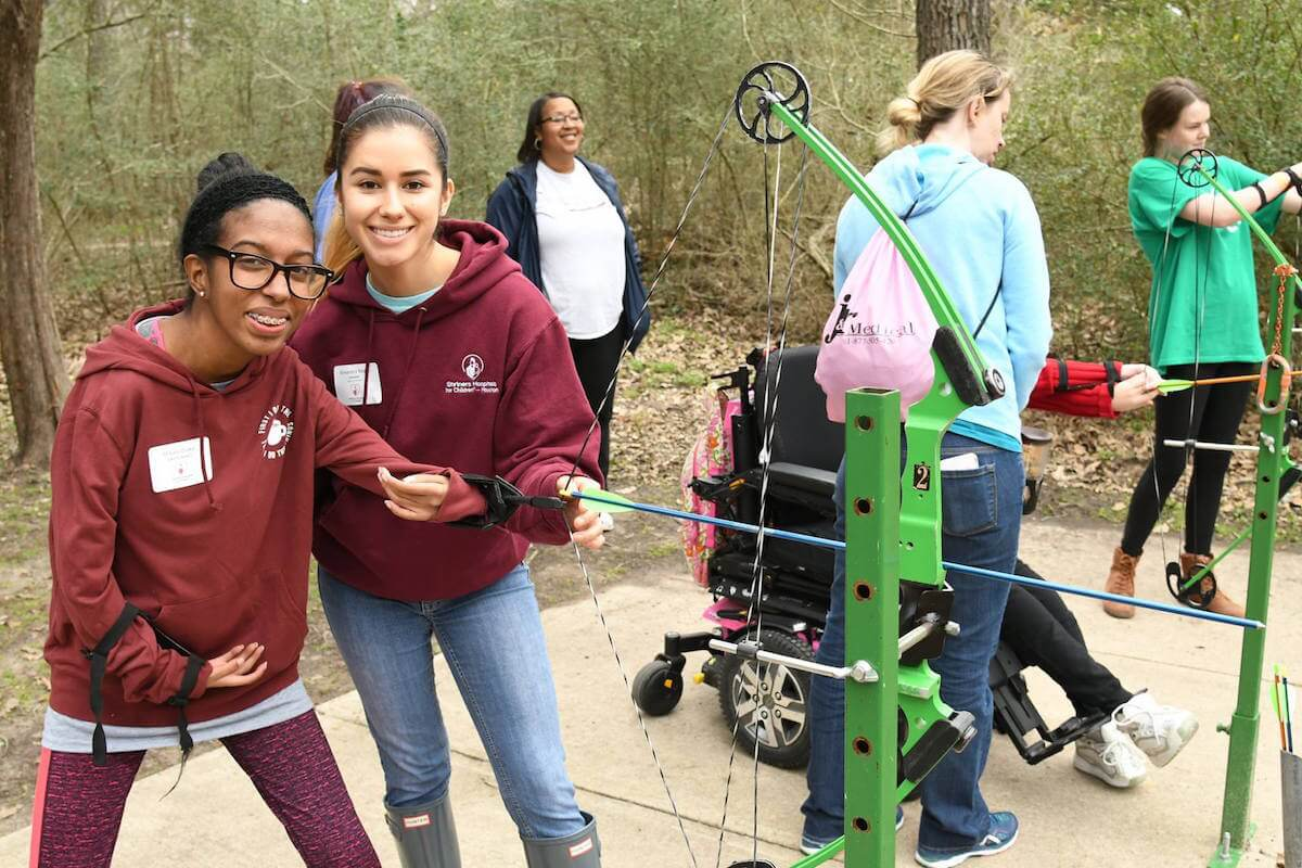 Makayla, a patient of Shriners Hospitals for Children - Houston, uses a bow and arrow with her physical therapist, Alexandra, at an annual camp that allows patients to participate in various activities.