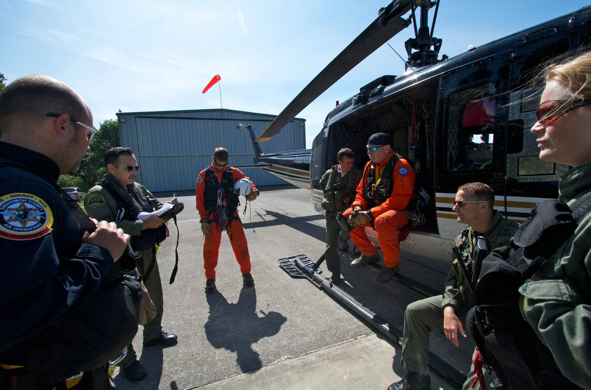 The team's pilot in charge (left in green) leads a pre-mission briefing at a helicopter base in Snohomish, Washington. Pre-mission briefings are conducted every time to help mitigate the team's risk.