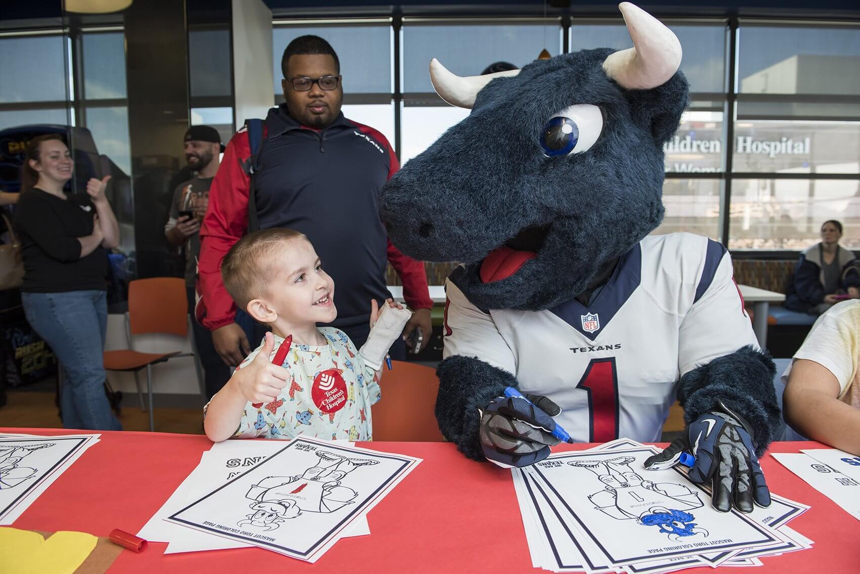 Jeremiah Greer gives Texans mascot Toro a big grin. (Credit: Allen S. Kramer/Texas Children's Hospital)