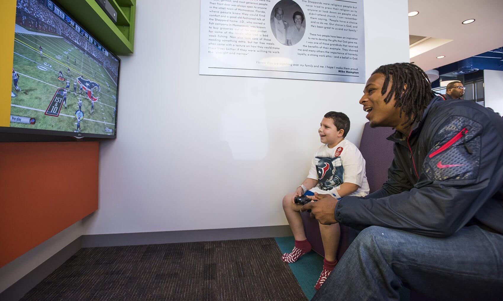 Safety Lonnie Ballentine plays a video game with Dylan Tindall. (Credit: Allen S. Kramer/Texas Children's Hospital)