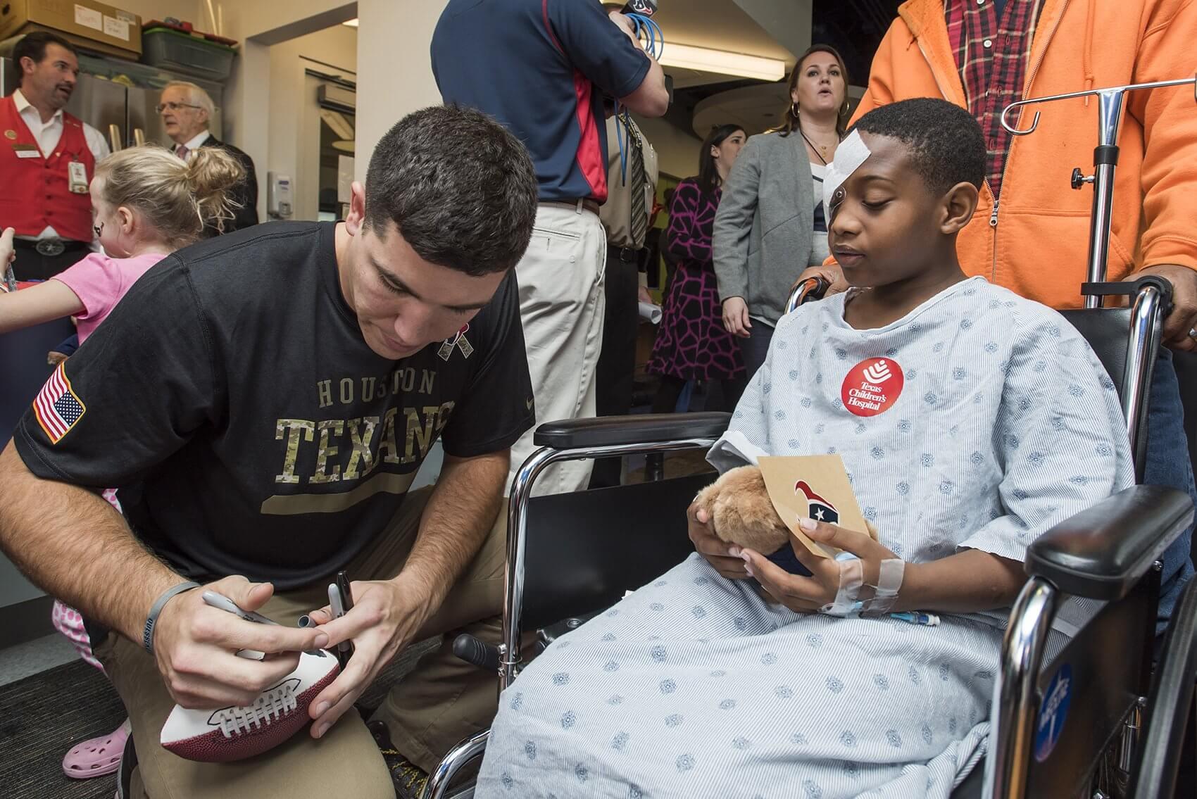 Texans tight end Ryan Griffin autographs a football. (Credit: Allen S. Kramer/Texas Children's Hospital)