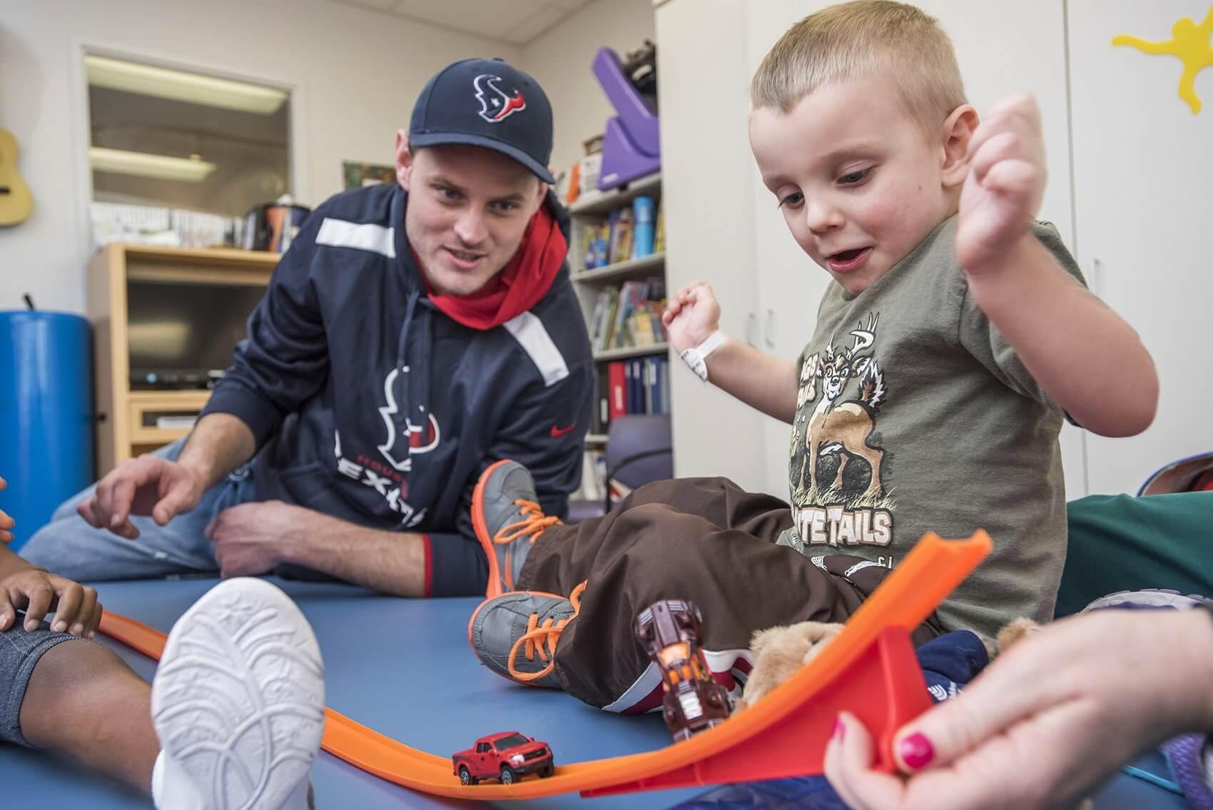 Braydon Nelson demonstrates his race car skills for Texans quarterback Ryan Mallett. (Credit: Allen S. Kramer/Texas Children's Hospital)