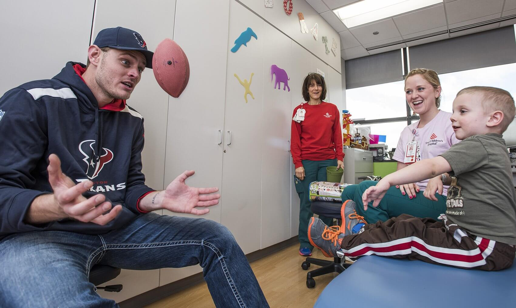 Quarterback Ryan Mallett shows Braydon Nelson how he makes a catch. (Credit: Allen S. Kramer/Texas Children's Hospital)