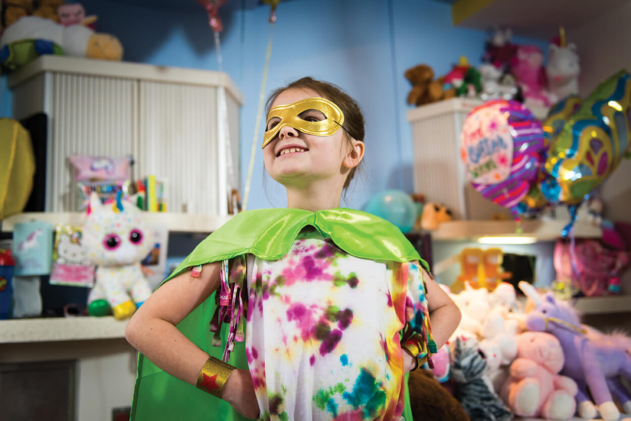 "Texas Children's Hospital patient Ella Garner strikes a pose in September, when TEXAS CHILDREN'S CANCER CENTER and other TMC hospitals, participated in ""going gold"" to honor all the brave superheroes fighting cancer during National Childhood Cancer Awareness Month. (Credit: Allen S. Kramer / Texas Children's Hospital)"