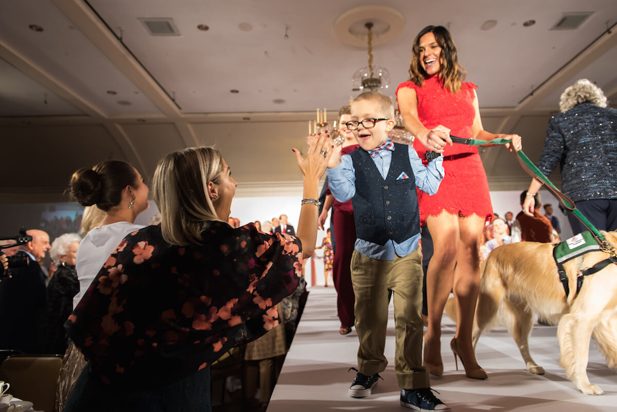 Patient Max Boatwright and Sarah Herbek, animal assisted therapy coordinator at Texas Children's Hospital, walk therapy dog Elsa down the runway at the 11th annual Celebration of Champions luncheon and fashion show. (Credit: Allen Kramer, Texas Children's Hospital)