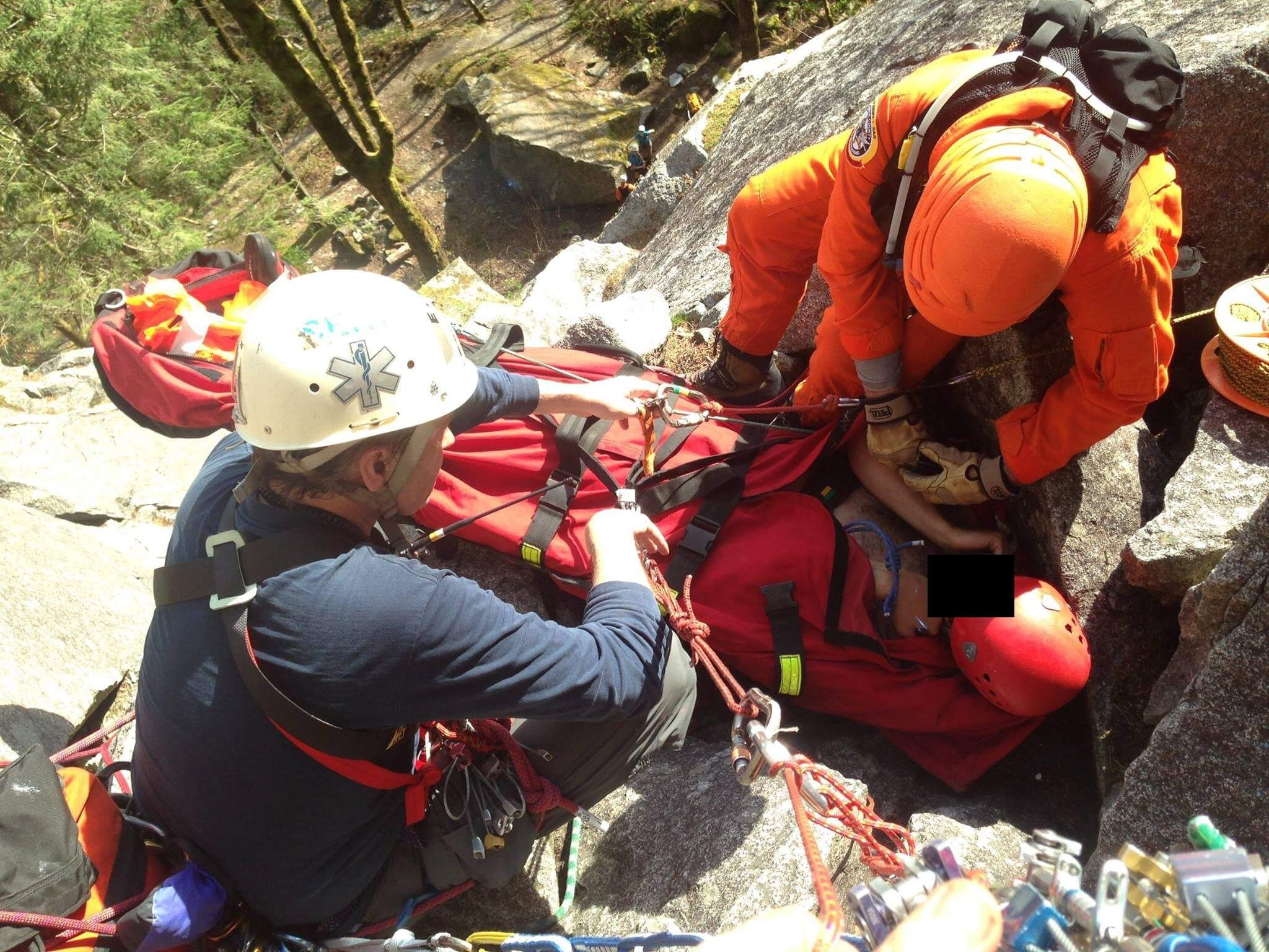 McDonough (in orange) provides patient care for an injured climber on a rock ledge in Index, Washington. He and his team located the climber and and coordinated a helicopter extraction via hoist from his location.