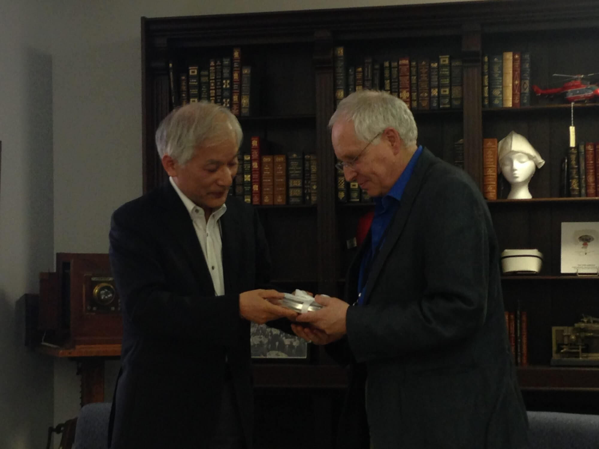 Masahito Ando, Ph.D., a professor at Gakushuin University in Tokyo, Japan, presents Philip Montgomery, MLIS, CA, head of the TMC Library's McGovern Historical Center, with a hard drive of digitized documents from the Atomic Bomb Casualty Commission.