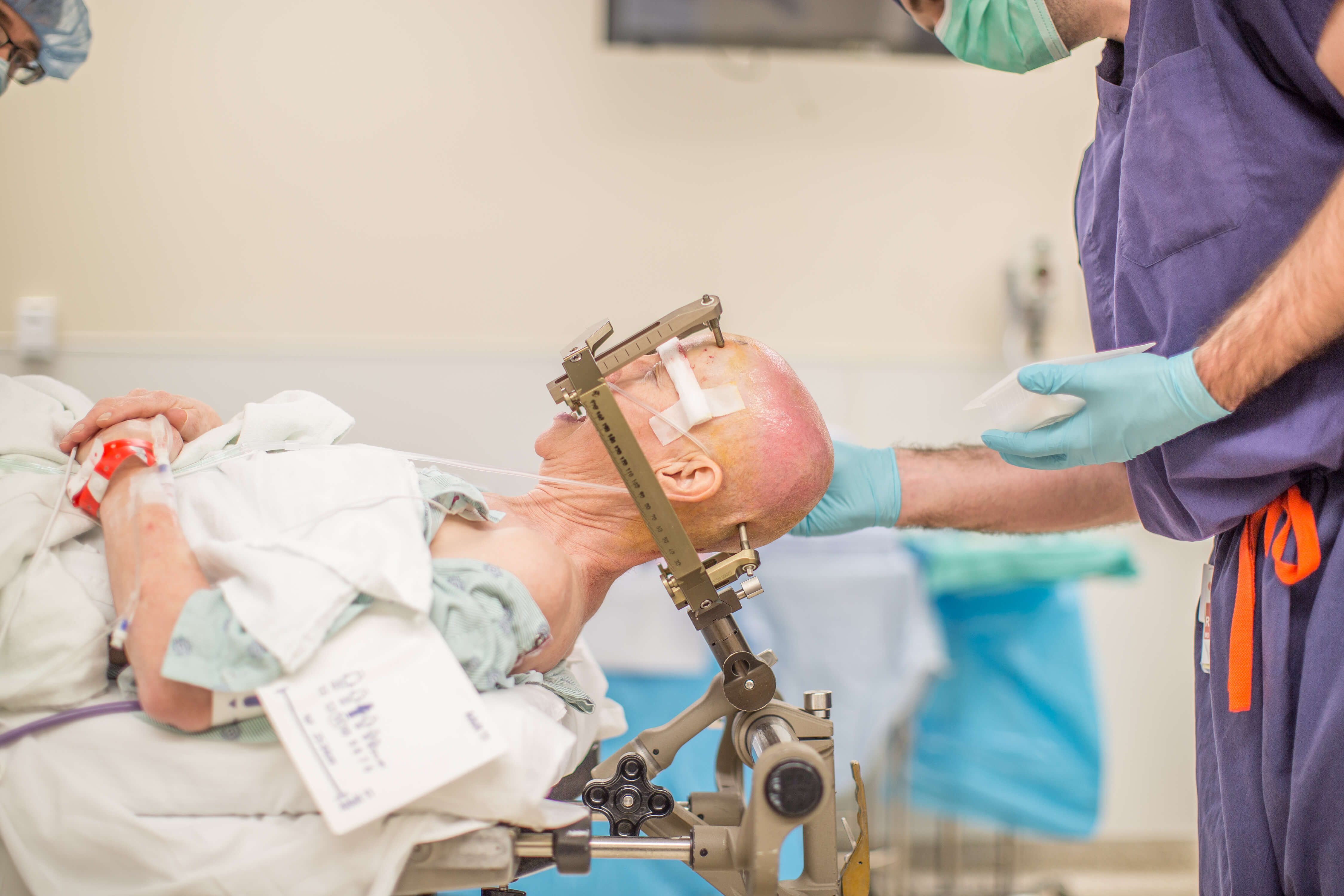 Anna Henry lies on her back on an operating room table with a metal frame around her head as she is prepped for surgery.