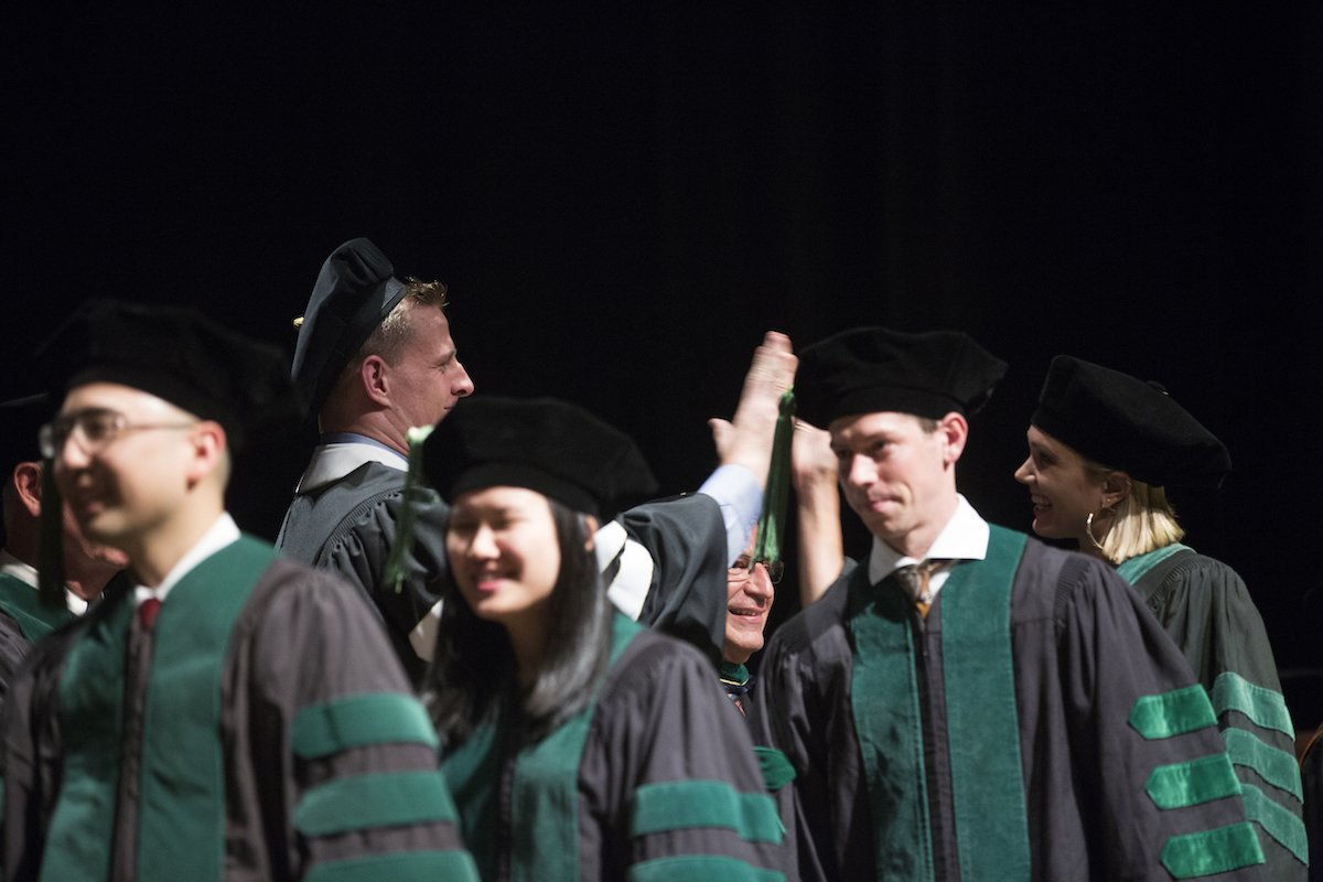 J.J. Watt high fives the new doctors as they walk across the stage.
