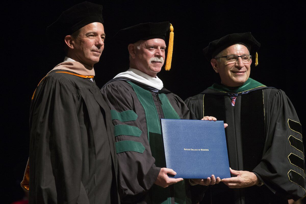 Dr. Persse receives his honorary degree from Dr. Paul Klotman and Fred R. Lummis, Chair of the Board of Trustees at BCM.
