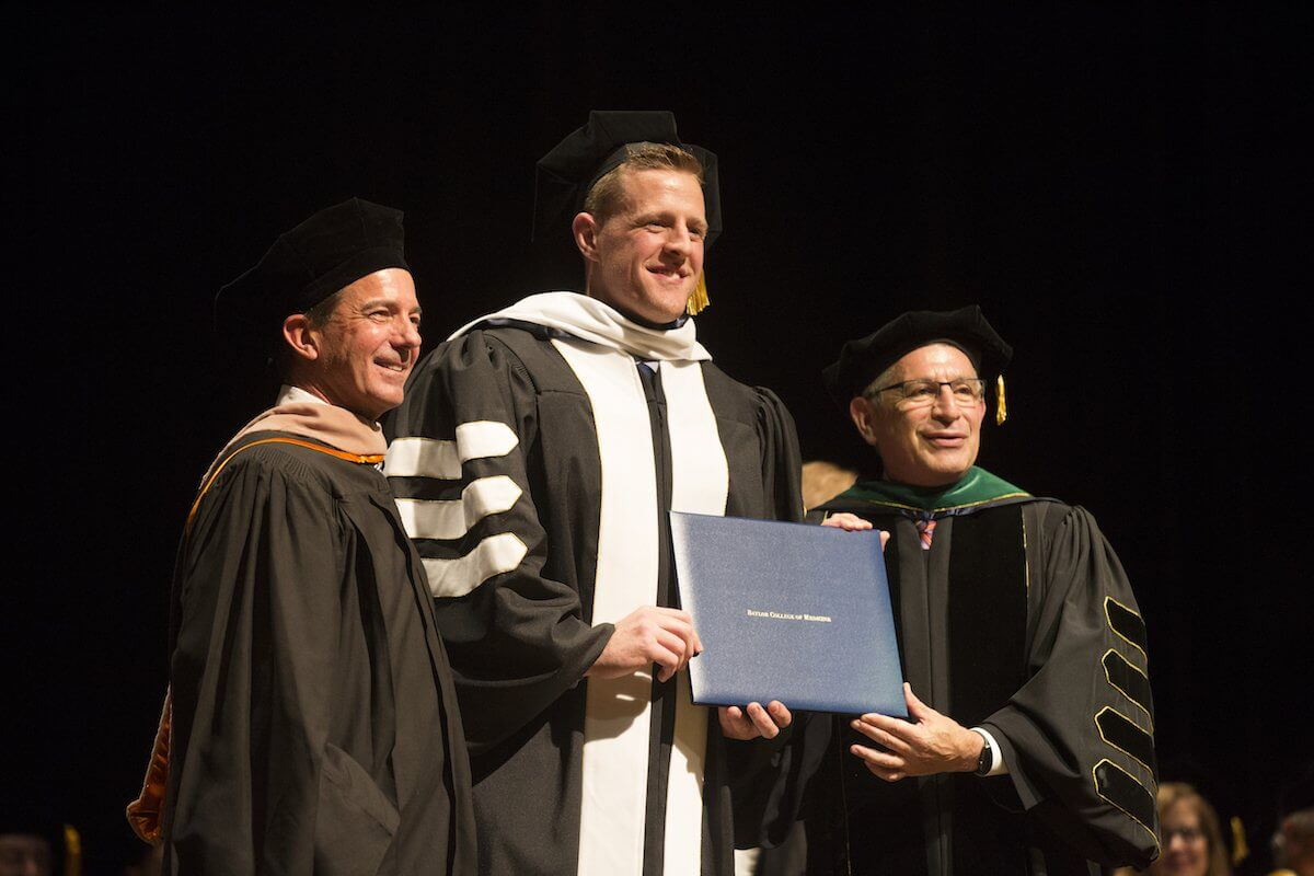 J.J. Watt receives his honorary Doctorate of Humanities Degree from Dr. Paul Klotman and Fred R. Lummis, Chair of the Board of Trustees at BCM.