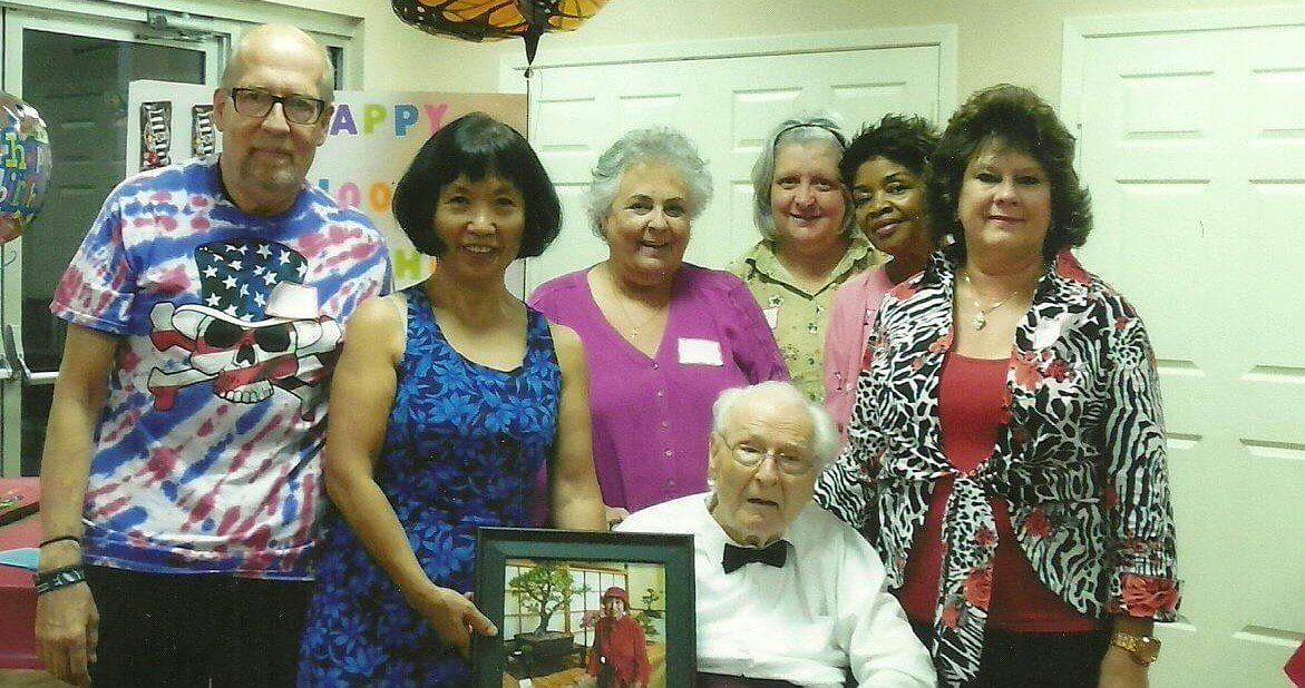 """Seated at center, Walter """"Brownie"""" Brown is joined by fellow members (from left to right): Howard Burgner, Yoko Hirose (pictured holding a photo of her mother, Kikuko Hirose), Marta Josserme, Mary Ann Davis, Patricia Hill and Marilyn Grandy."""