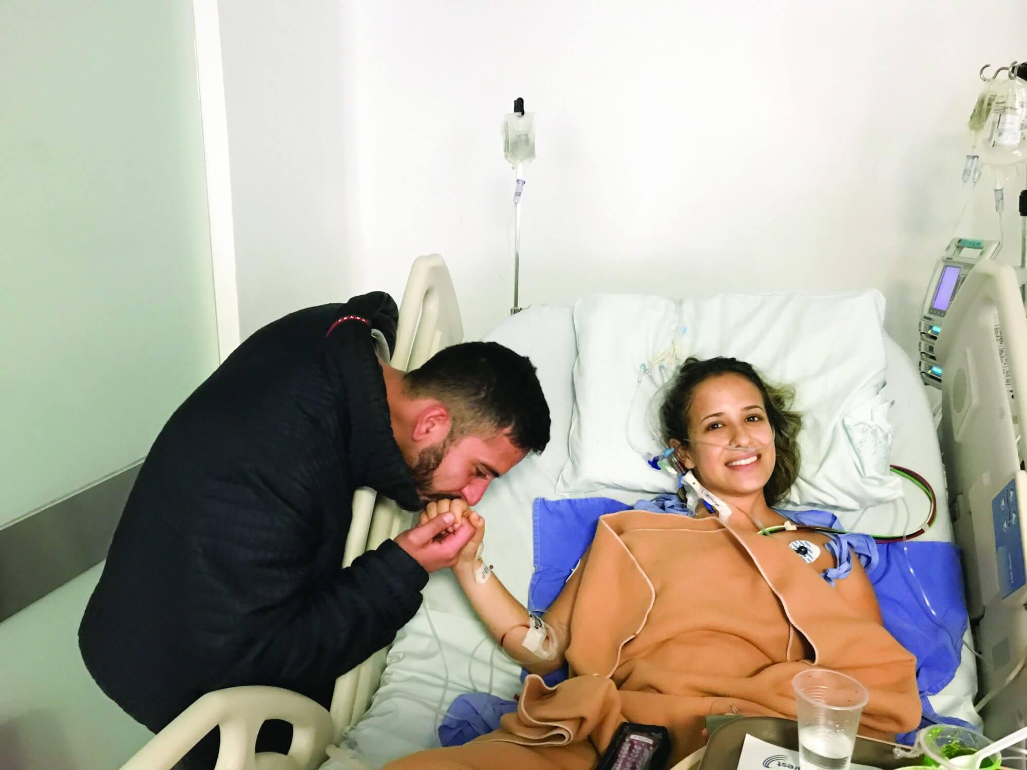 Laura Caicedo's fiancé, Julian Cortes, kisses her hand after her heart surgery.