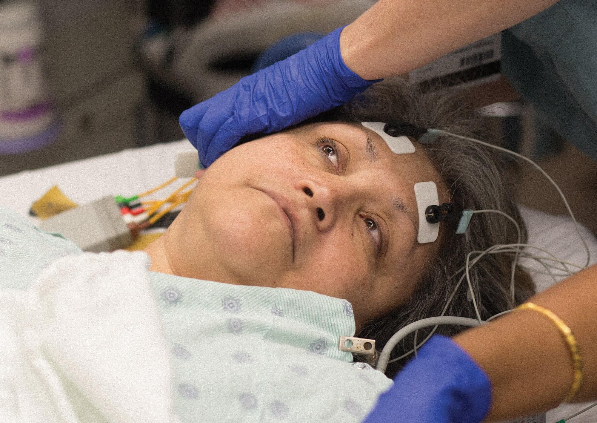 A nurse places electrodes on Natalia Rodriguez's forehead, prepping her for bilateral ECT treatment.