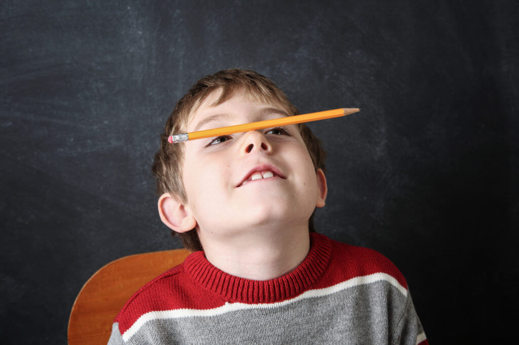 Young bored boy balancing a pencil on his nose.