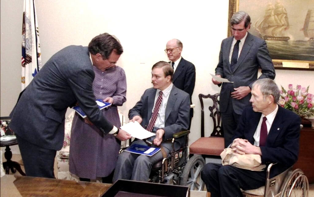 President George H.W. Bush accepts a proposal for the Americans with Disabilities Act from Houston disability rights activist Lex Frieden, center, in January 1986. (White House photography/Courtesy of Lex Frieden)