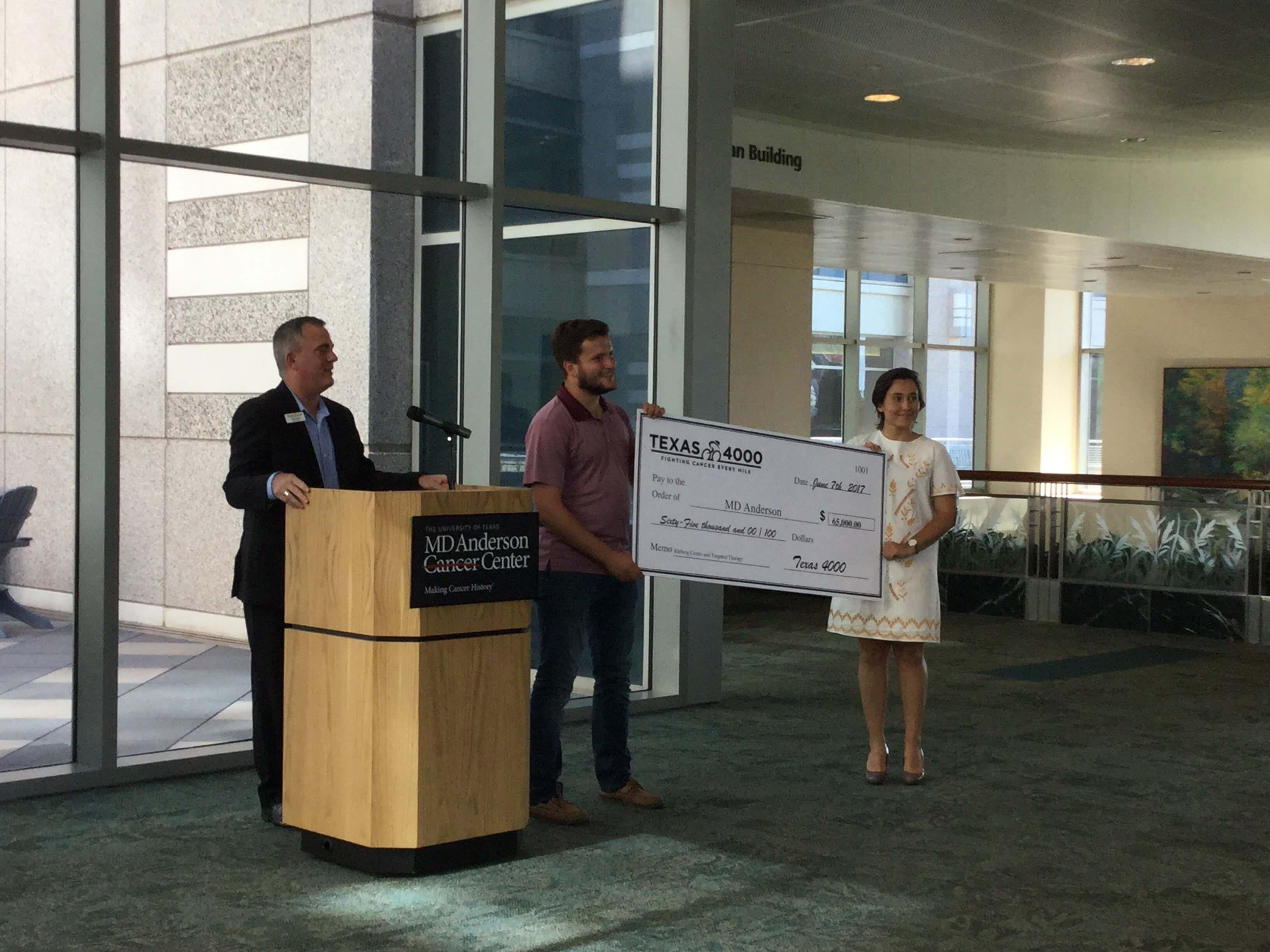 Texas 4000 riders present a $65,000 check to MD Anderson that caps off their goal to donate $1.5 million for cancer research at the hospital.