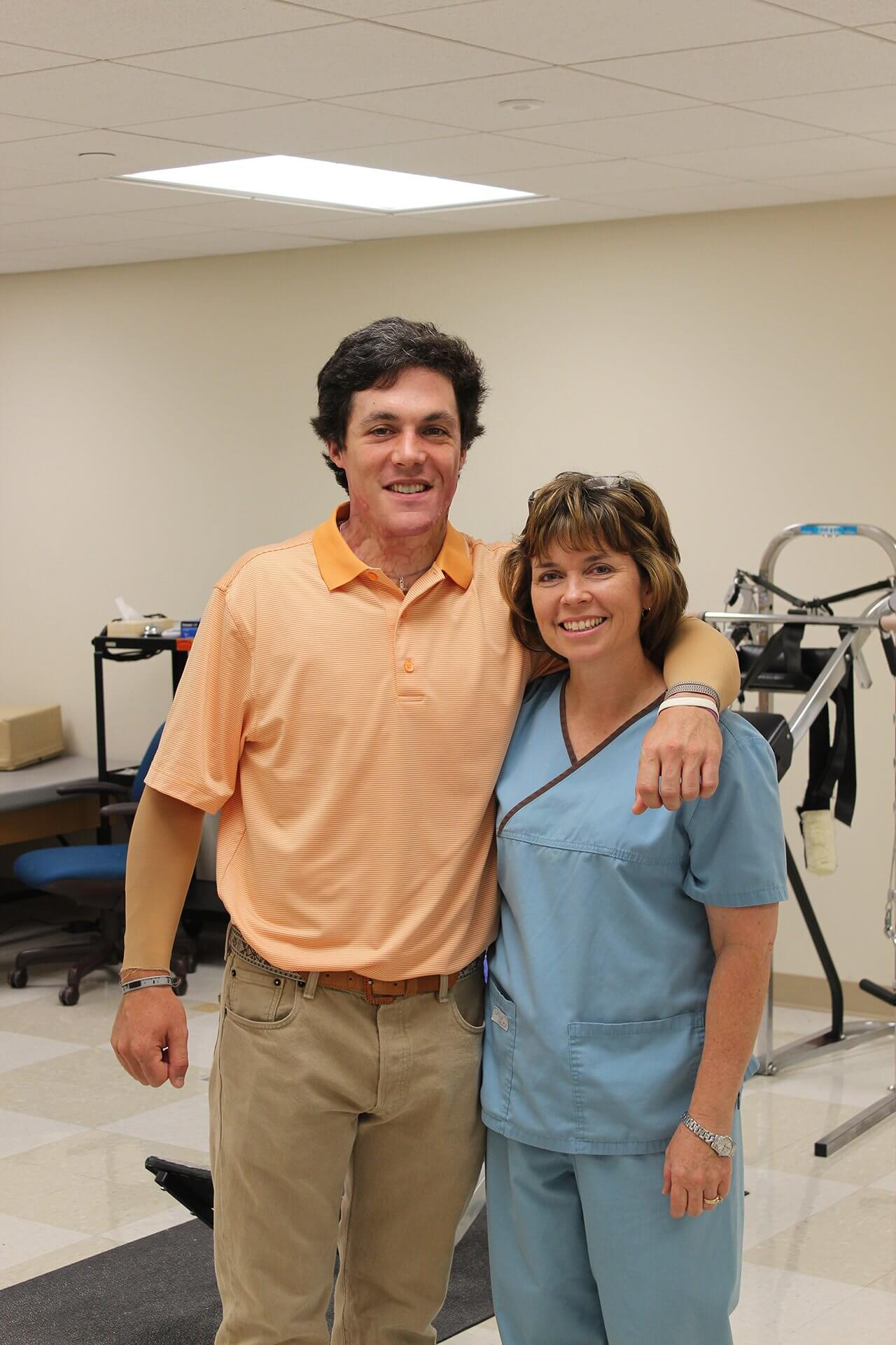 James Burke, left, poses for a picture with his occupational therapist Kimberly Walker, OTR, in the rehabilitation gym at Memorial Hermann-Texas Medical Center