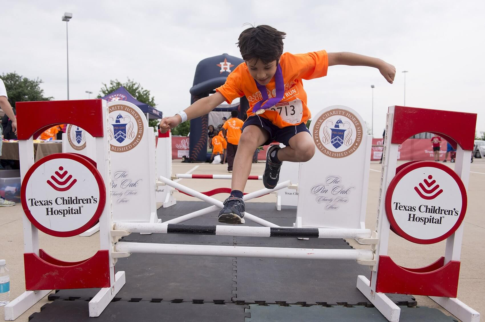 A participant jumps over the hurdles at Pin Oak Charity Horse Show's booth at the Family Fun Zone (Credit: Paul Vincent Kuntz/Texas Children's Hospital)