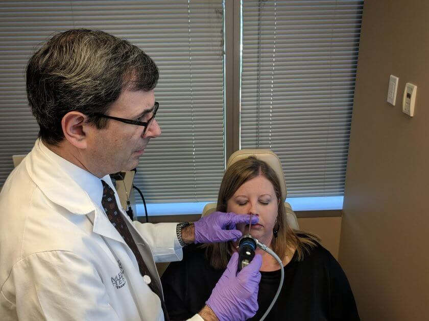 Martin Citardi, M.D., chair of the Department of Otorhinolaryngology–Head and Neck Surgery at McGovern Medical School at UTHealth, examines Carrie Owen's nasal implants.