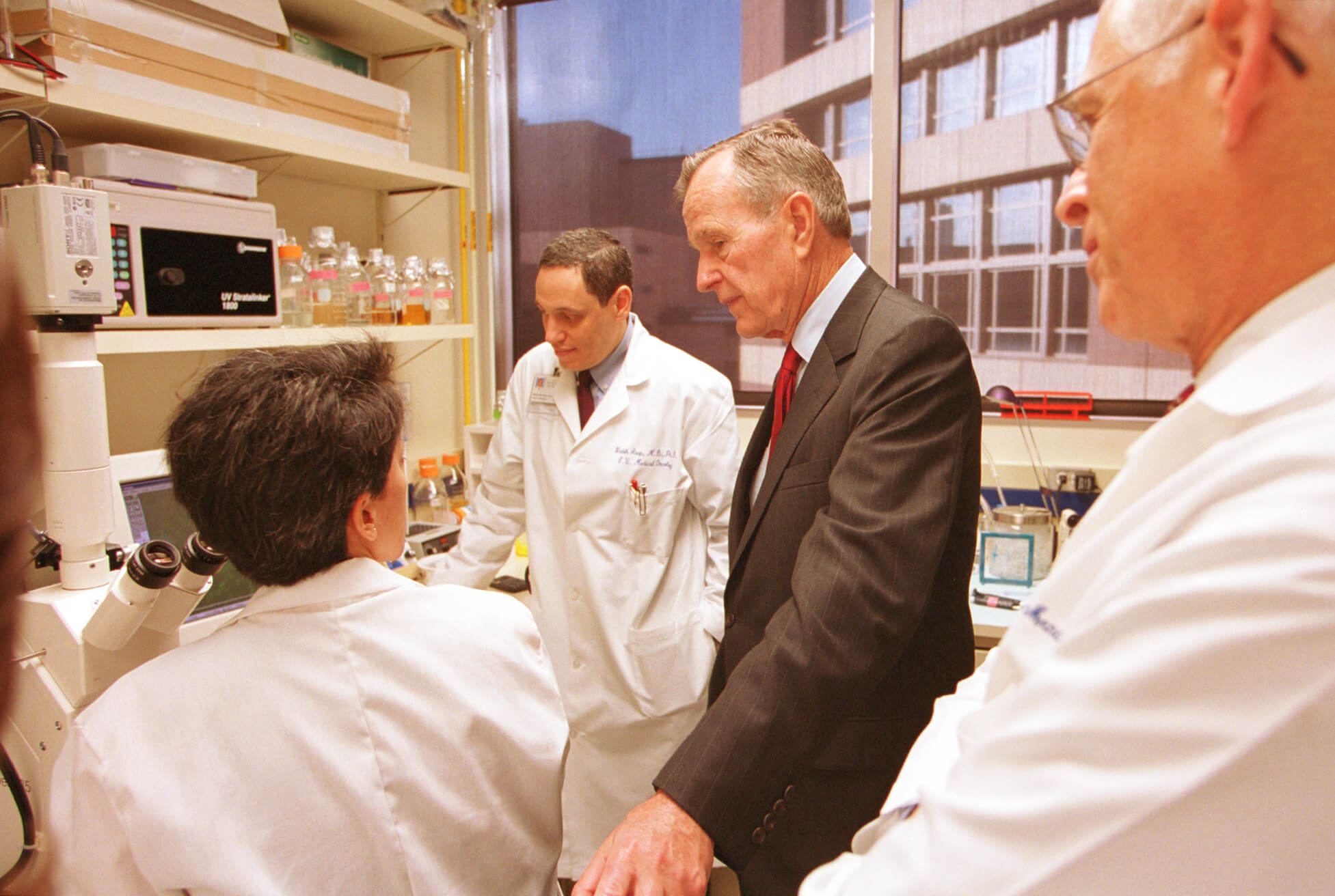 Former President George Bush tours the University of Texas MD Anderson Cancer Center in 2001 and talks with researchers about tumors in test mice as then-President John Mendelsohn, M.D., right, observes. (Courtesy of MD Anderson)