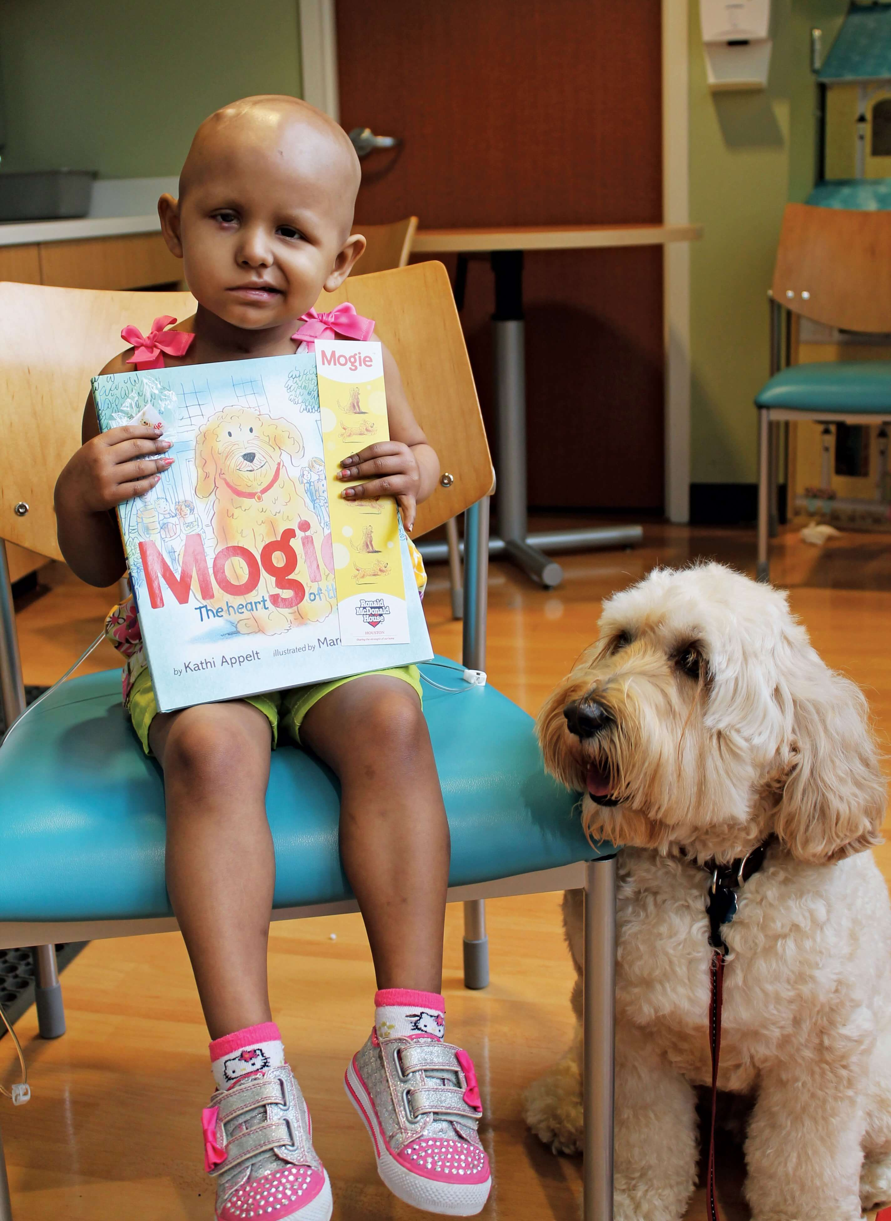 "The original Mogie, in his younger years, with a patient holding ""Mogie: The Heart of the House""— the children's book that helped the Labradoodle reach celebrity status."