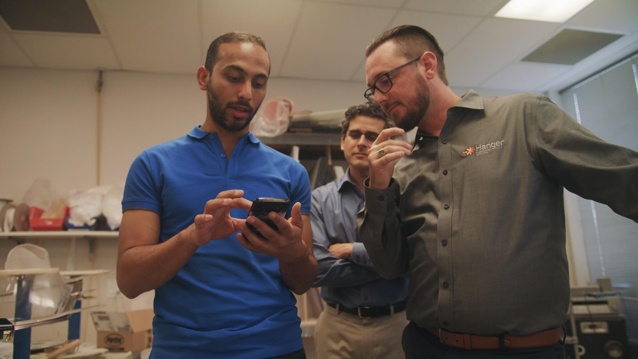 AT&T's Mohamed Elmahdy, left, shows Andrew Dibello, right, and Aaron Flores, center, the prototype mobile application.