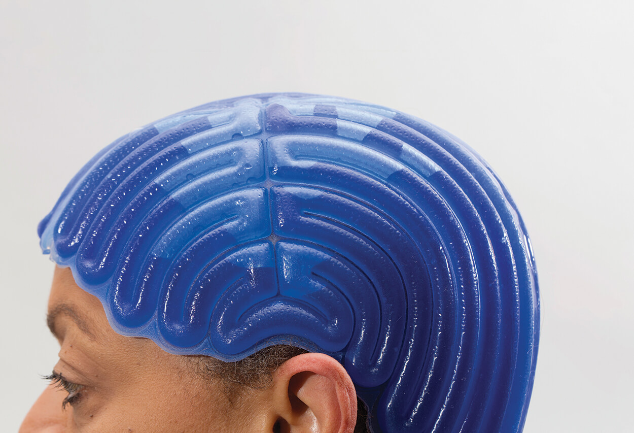 A blue cap made of silicone, connected to the Paxman Cooling System, is fitted to the patient to cool the scalp as they receive chemotherapy treatment.