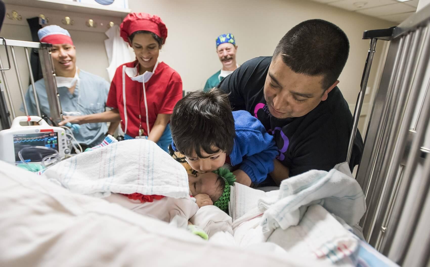 Big brother Azariah kisses his sisters before surgery. (Credit: Allen S. Kramer/Texas Children's Hospital)