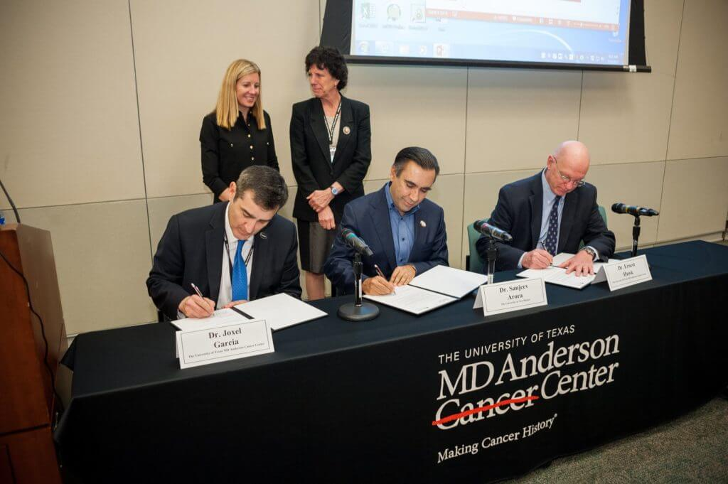 Sanjeev Arora, director of Project ECHO, signs an agreement with MD Anderson Cancer Center