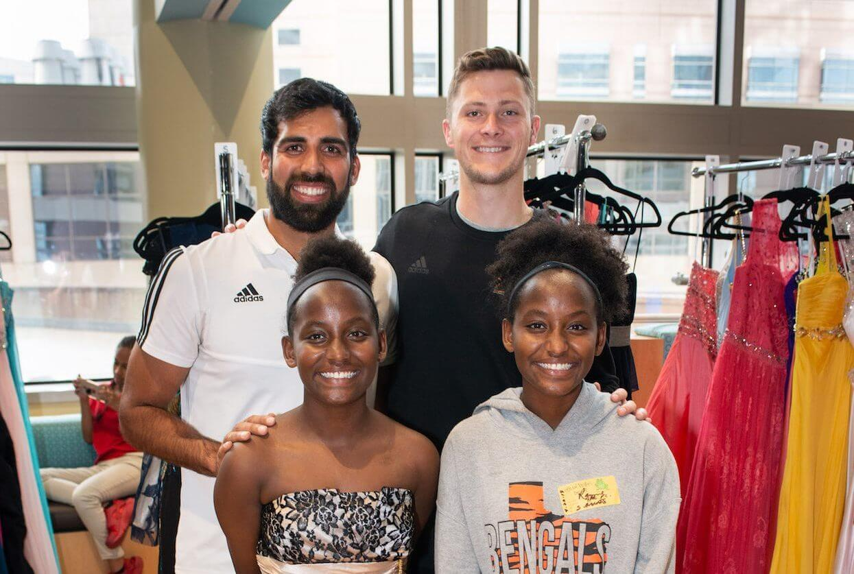 Aaliyah Parker, left, tries on dresses at the Prom Party Palooza Dress and Suit Shop with help from her twin sister, Rayne Parker, and Houston Dynamo players. (Photo courtesy of MD Anderson)