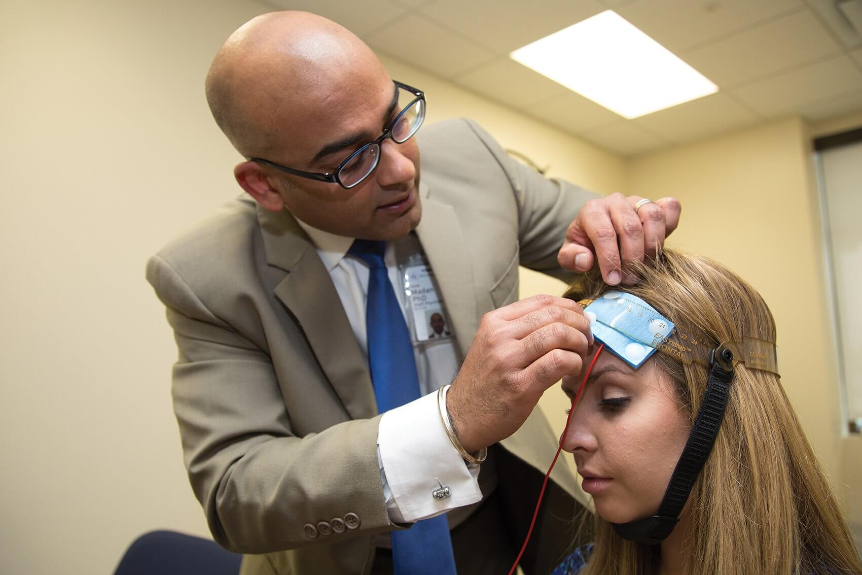 Madan demonstrates a transcranial direct current stimulation device, which is currently being tested in clinical trials for patient use and has been shown to effectively treat chronic pain, depression and anxiety.