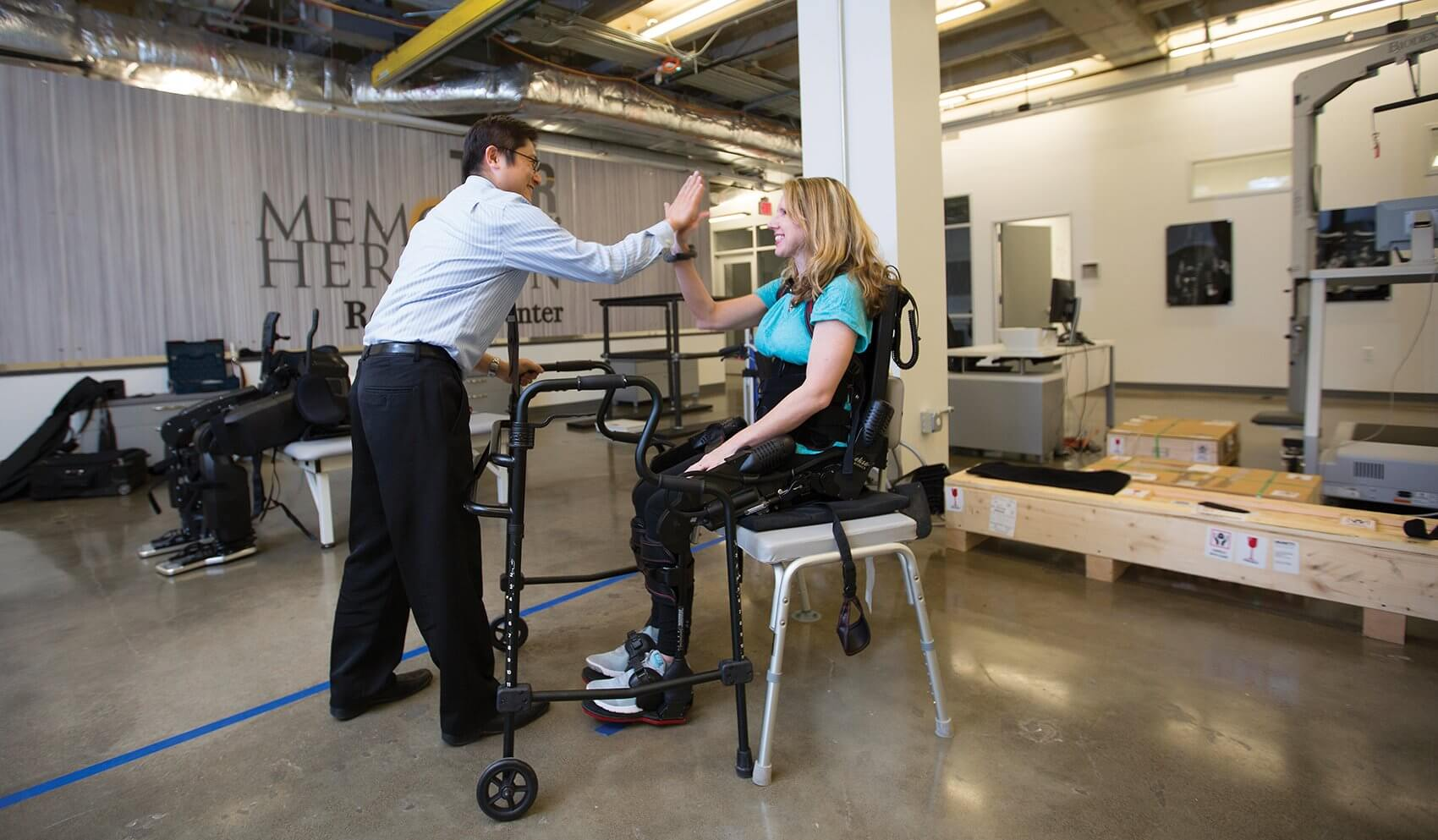 """Shuo-Hsiu """"James"""" Chang, Ph.D., and patient Kelly Davis celebrate a successful session of walking laps around the NRRC floor in the Ekso exoskeleton."""